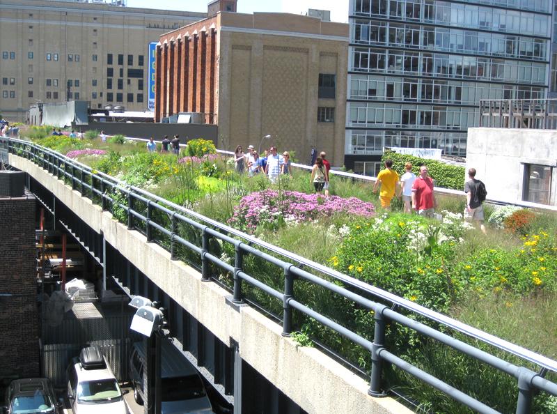 写真:高架橋を緑道公園にしたハイラインの写真。野趣溢れる様々な花が咲く小道を多くの人々が歩いている