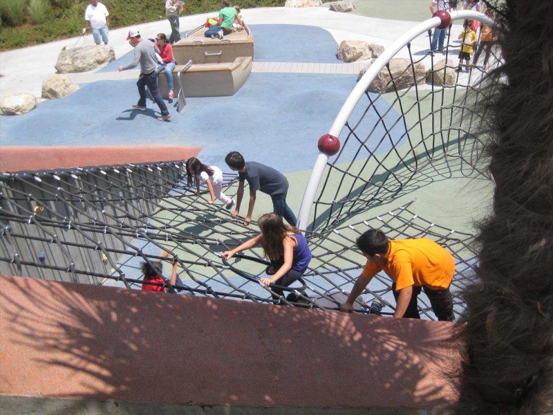 写真:切り欠いた山の一部のネットクライムを登る子どもたち