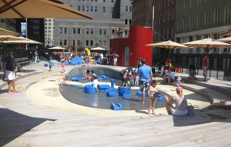 写真:遊び場の内部。地面は板張りで中央に深さ10センチ程度の水場。多数のウレタンフォームのブロックとそれで遊ぶ子どもたち