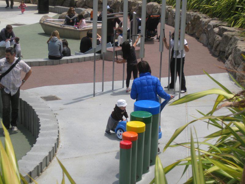 写真:楽器遊具のエリア。5本の円柱型ドラムと、金属製のパイプが立ち並んだチャイム。子どもたちが付属のマレットで演奏中