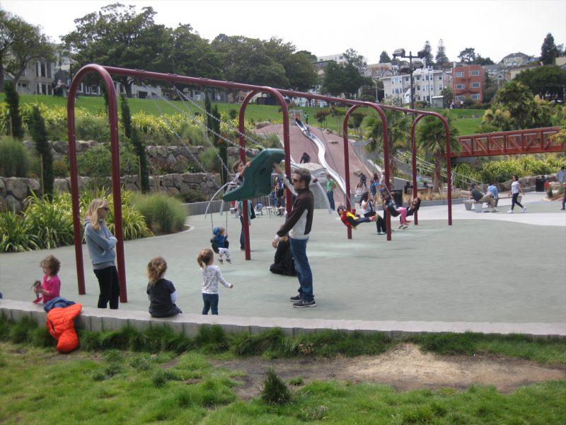 写真:高い梁に6つのシートが並んだブランコエリア。背もたれ付きのブランコには幼児が乗っており、大人が大きく揺らしている。