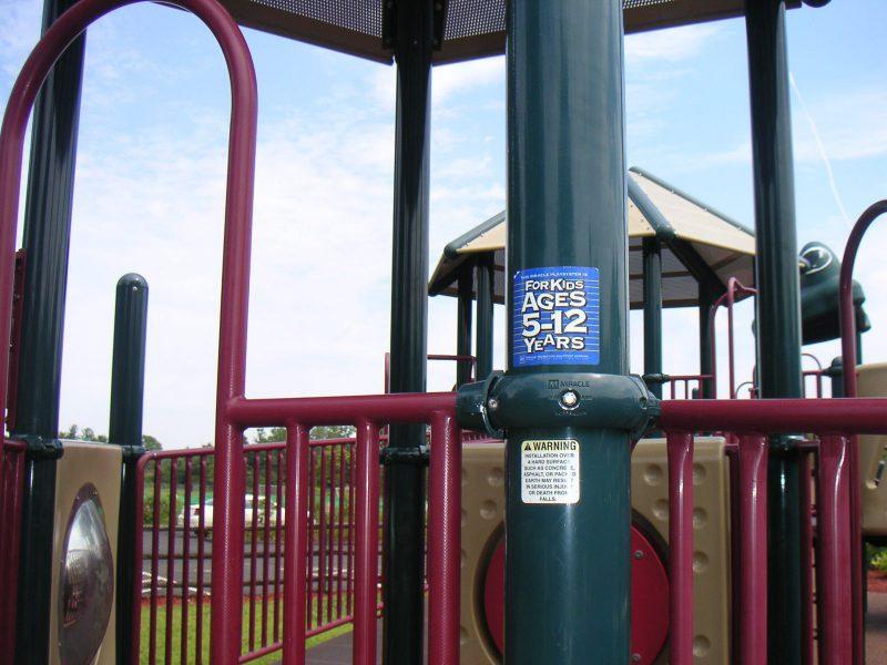 写真:複合遊具の柱に貼られた対象年齢表示シール「5~12歳用」