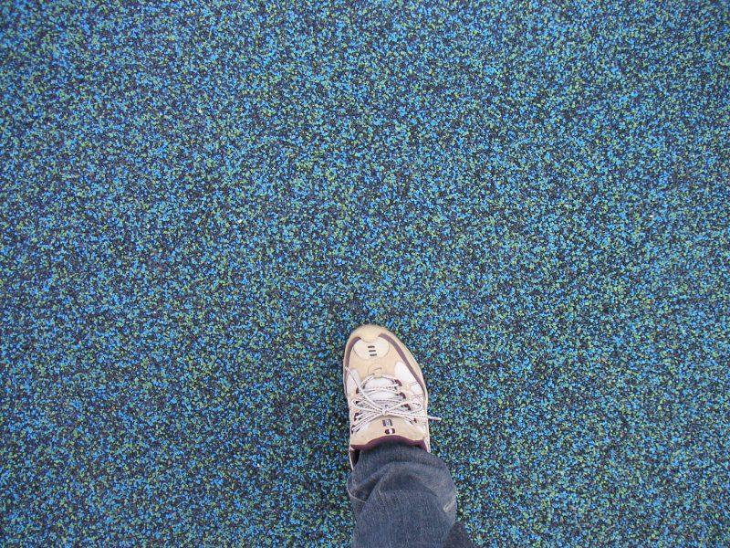 写真:細かいチップが敷き詰められた地面と撮影者の足