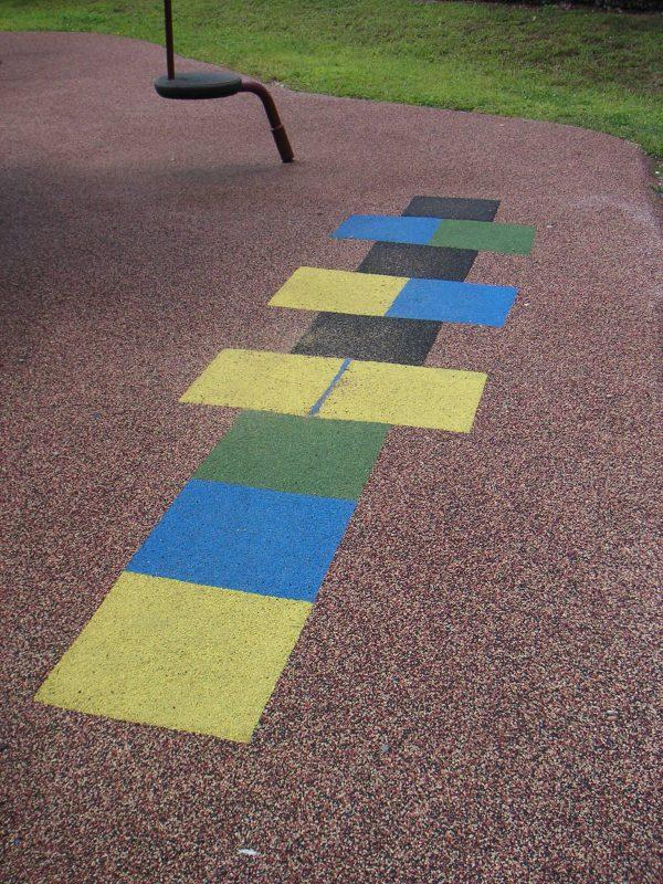写真:地面に描かれた異なる色の四角。片足で跳ぶケンケンパの遊びを誘う