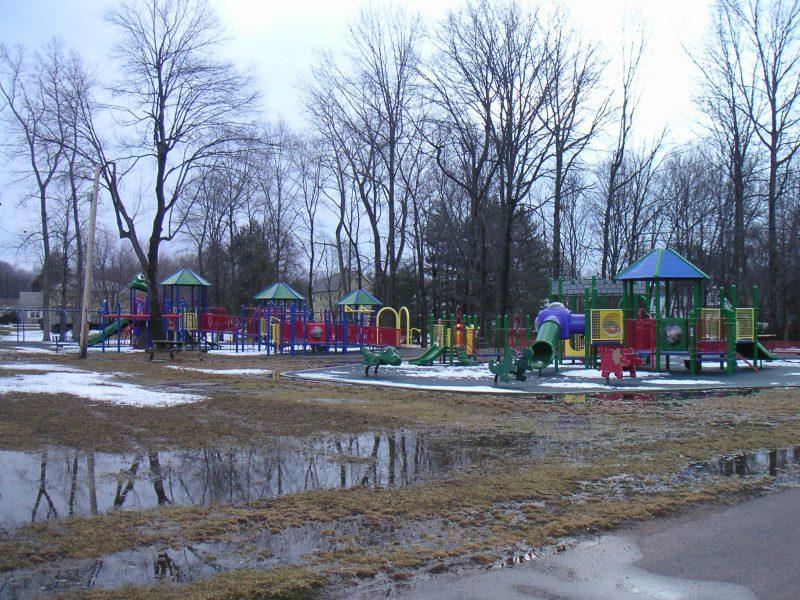写真:葉の落ちた木立の前にある遊び場。さらに手前には雪と水溜りの残る芝生