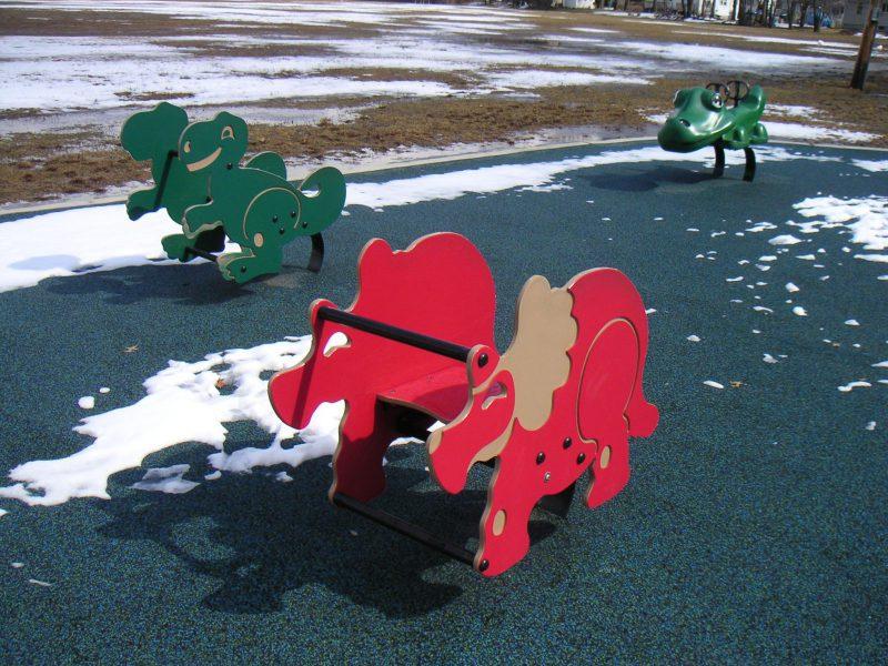 写真:ゴム舗装の遊び場にあるスプリング遊具。陽が差している