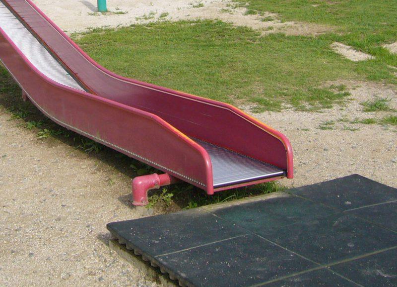 写真:滑り台の降り口に敷かれたゴム舗装のパネル。地面から5センチ以上突出している
