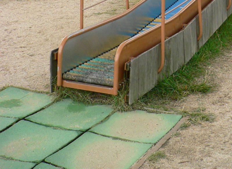 写真:滑り台の降り口に敷かれたゴム舗装のパネル。各パネルが湾曲し波打った状態