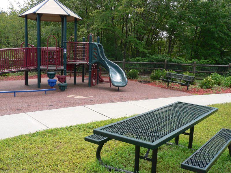 写真:遊具やベンチが置かれた公園の一画。地面には様々な素材が使われている