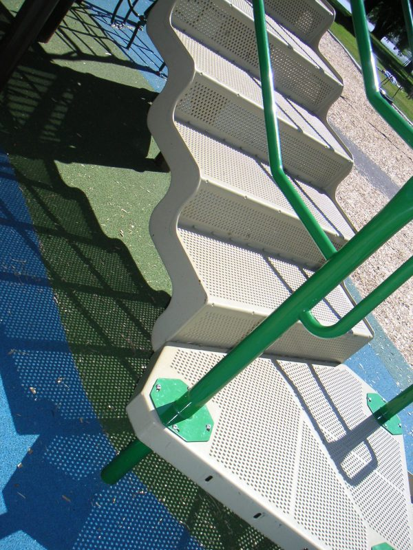 写真:複合遊具の階段。細かい穴の開いた床の影が地面に映っている