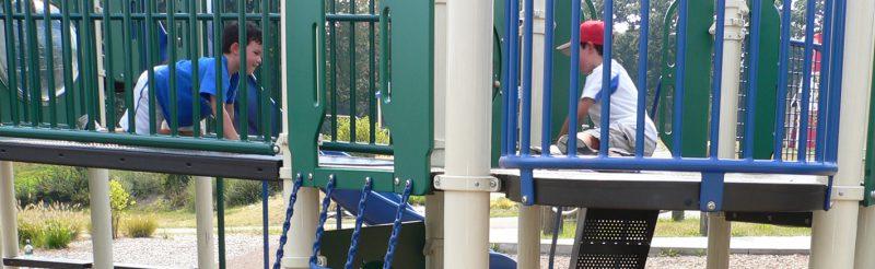 写真:複合遊具のデッキに座り込みプレイパネルで遊ぶ男の子。通路を笑顔で這いながら彼に近づく友達