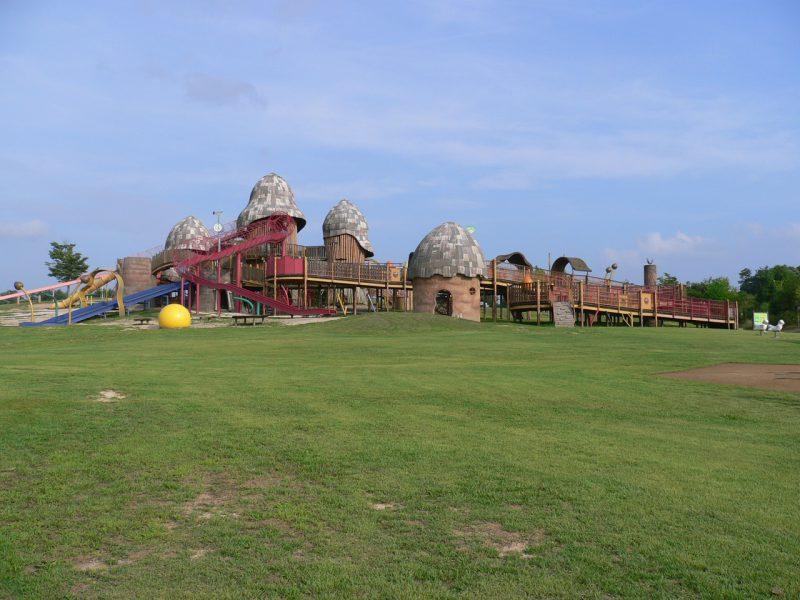 写真:青空をバックに、芝生の丘の斜面に建つ大型複合遊具