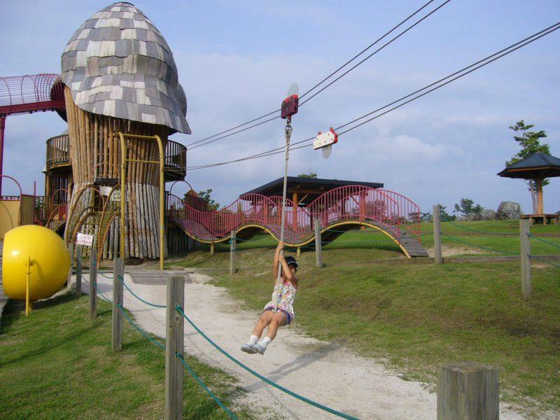 写真:ターザンロープにぶら下がって遊ぶ女の子