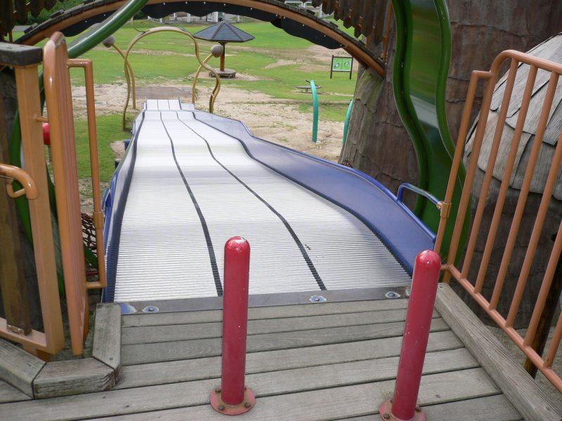 写真:幅広のローラー滑り台のスタート地点。手前に2本の赤いポール