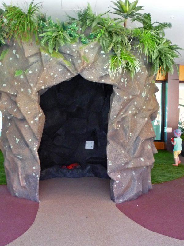 写真:直径2メートルほどの円柱が立っている。表面は岩壁風で、大きな入口から見える奥の暗い岩棚は一部が赤く光っている