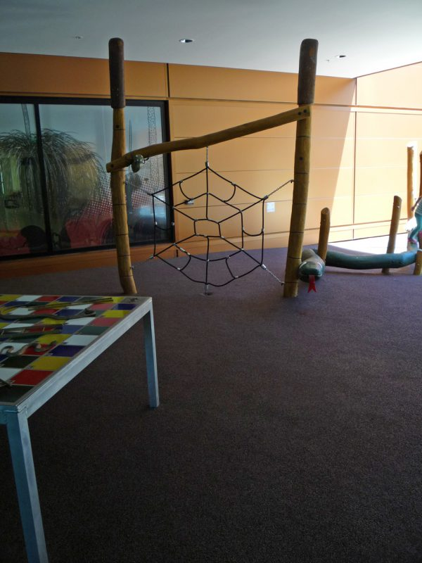 写真:垂直に張られたクモの巣状のネット遊具。ユーモラスな蛇の形の平均台