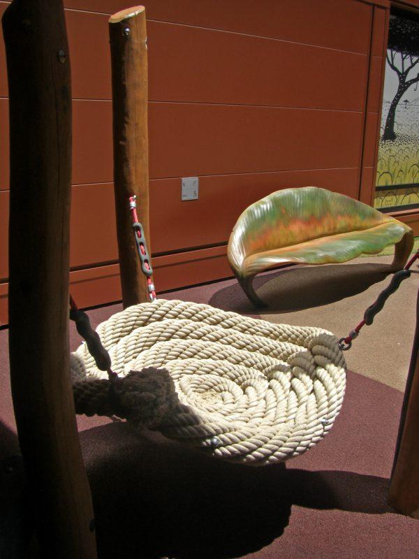 写真:太い縄で編んだ大きな円い座布団のようなシートを3本の柱で吊り下げた遊具