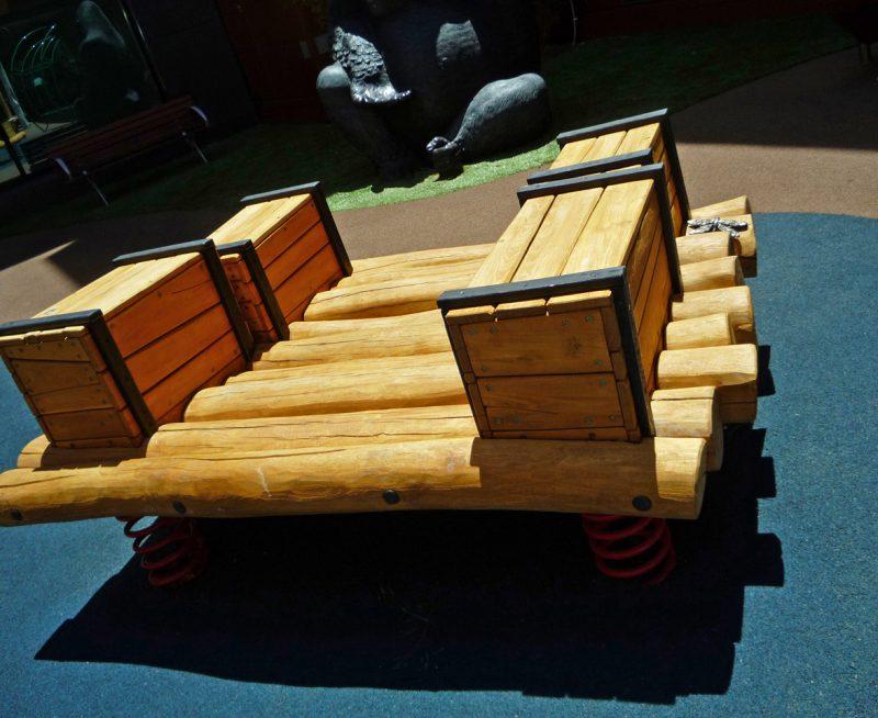 写真:丸太を組んだいかだの形の遊具。左右に木箱が2個ずつ並ぶ