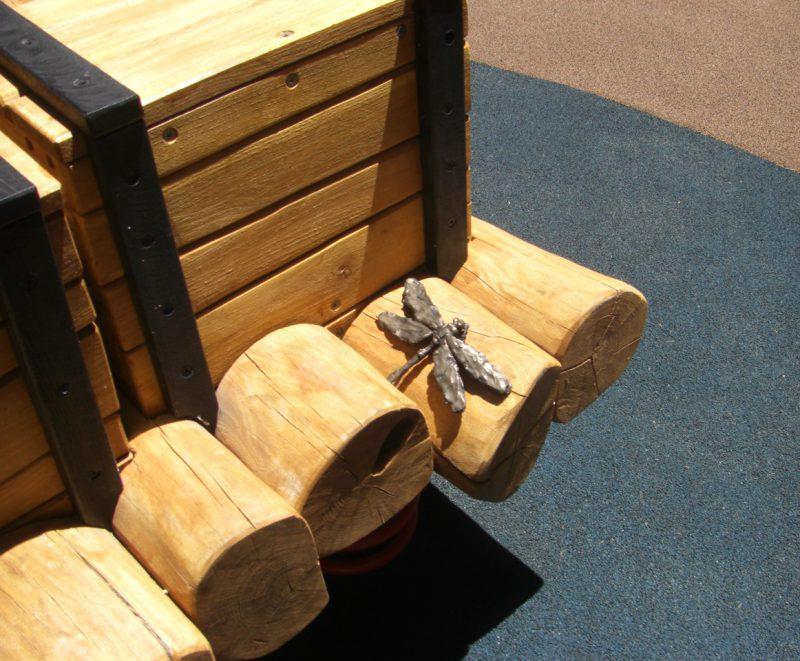写真:木箱の陰に、金属製のリアルなトンボ