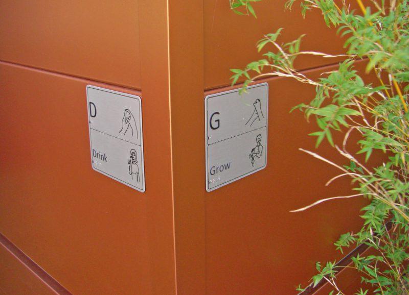写真:壁に貼られたパネル。上段はDの字と指文字、下段はDrinkの単語とその手話。字と単語の下には点字もある