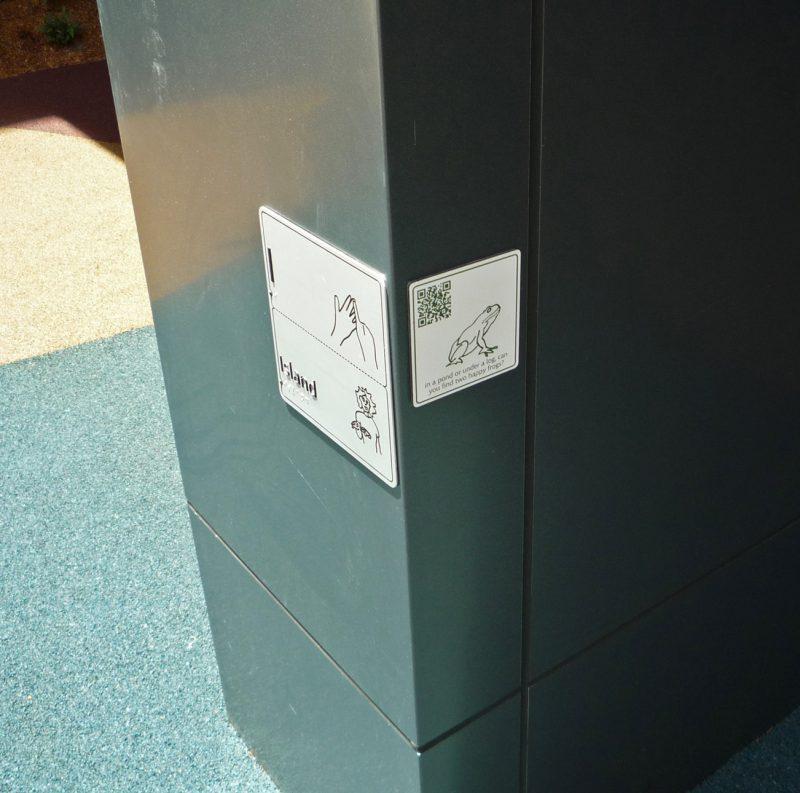 写真:柱に貼られたパネル。カエルの絵とQRコード