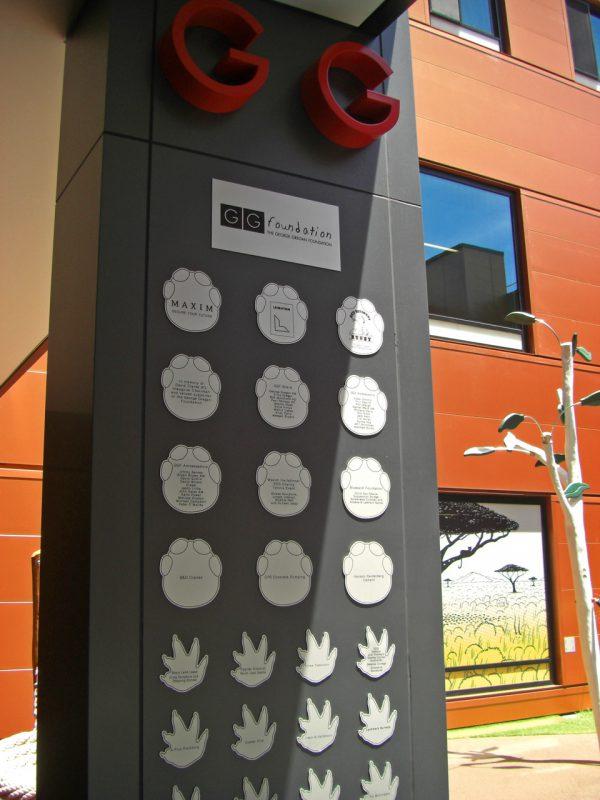 写真:柱に掲示された財団のロゴと、協力者の名前やメッセージが書かれたタイル
