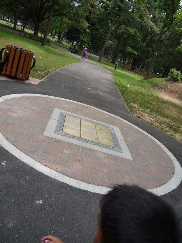 写真:2本の道が十字に交わる交差点の中央に、段差なく埋め込まれた遊具