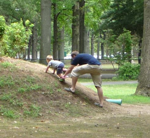 写真:丘を登ろうとする幼児と、サポートするお父さん