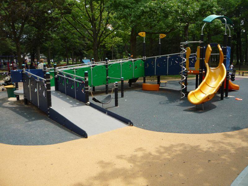 写真:スロープ付きの複合遊具。入り口に誘導するよう地面が着色されている