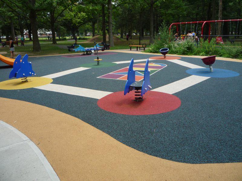 写真:五角形に配置された各種のスプリング遊具や回転遊具。中央の地面にはゲームに利用できる模様が描かれている
