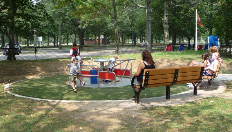 写真:回転遊具で遊ぶ子どもたち。そばのベンチでは母親たちがくつろいで見守る