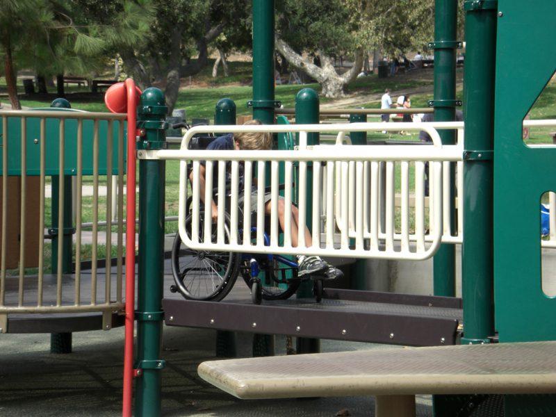 写真:複合遊具で車いすをこぐコール君