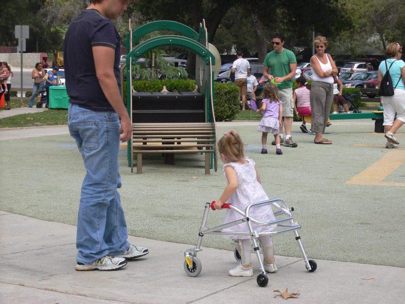 写真:足に装具をつけ歩行器で歩く小さな女の子