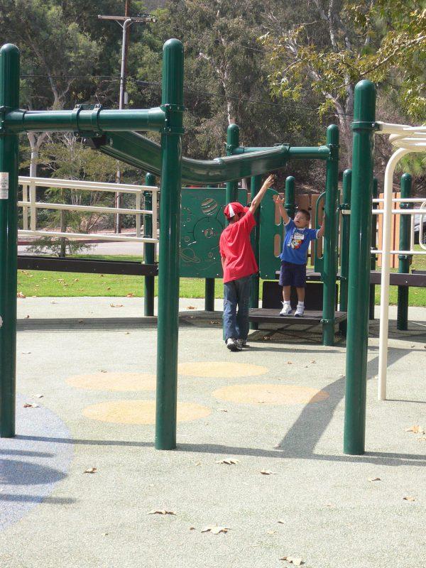 写真:吊り輪にぶら下がって頭上のレールをスライドする遊具のスタート地点にいる子どもたち