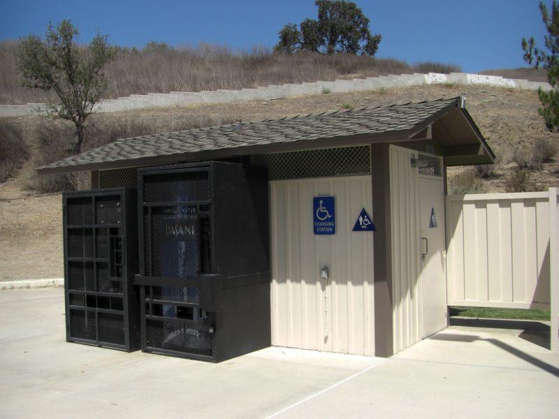 写真:トイレの建物の外に並んだ黒い大型の箱。隣には車いすマークの看板