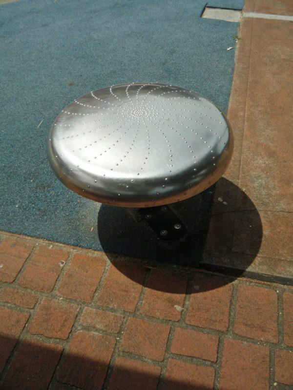 写真:ステンレス製のスツール。座面には隆起した点を並べて描いた渦巻のような模様