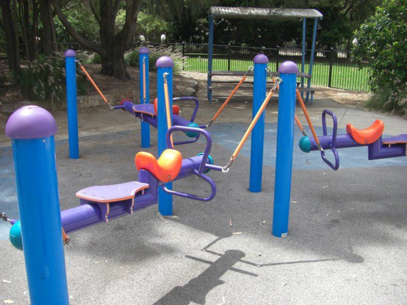 写真:小型の円柱の前後に座席を設け、4本の支柱から吊り下げた遊具。同じものが3つ中心に向き合うよう配置されている