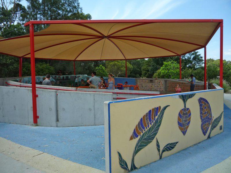 写真:回転遊具を覆う屋根と周囲を囲むコンクリート塀。正面の塀には壁画があり、葉の上の青虫、孵化している蛹、羽を広げた蝶の姿が表現されている