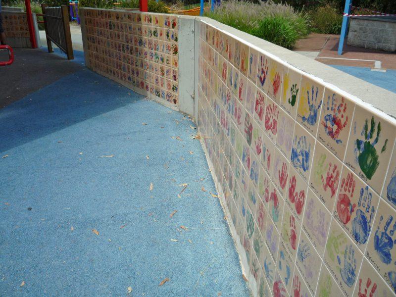 写真:塀の内側に並ぶカラフルな手形付きタイル