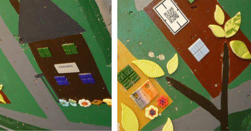 写真:描いた家の壁の部分に貼られた点字プレートやQRコードのプレート