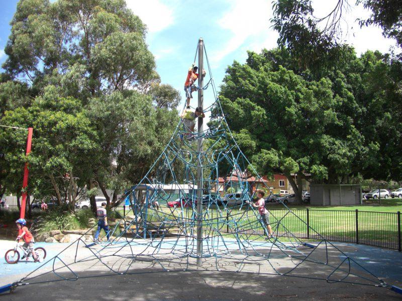 写真:四角錐の形にロープが張り巡らされた登り遊具。男の子たちが挑戦中