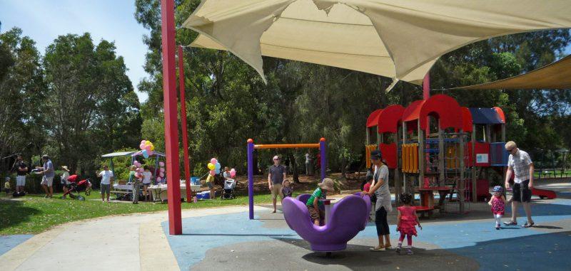写真:子どもたちが遊ぶ遊具エリアと、林のそばの草地にあるバーベキューコーナー。テーブルの周りには風船がいくつも飾り付けられ、人々が食事を楽しみながら談笑中