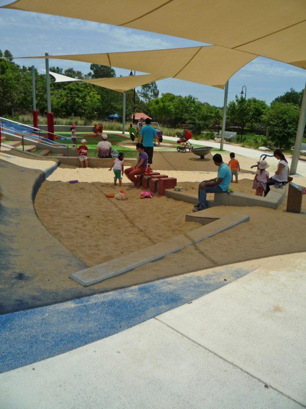 写真:頭上にシェードがある砂場。日陰で遊ぶ子どもたちと砂場の縁に腰掛けて見守る親たち