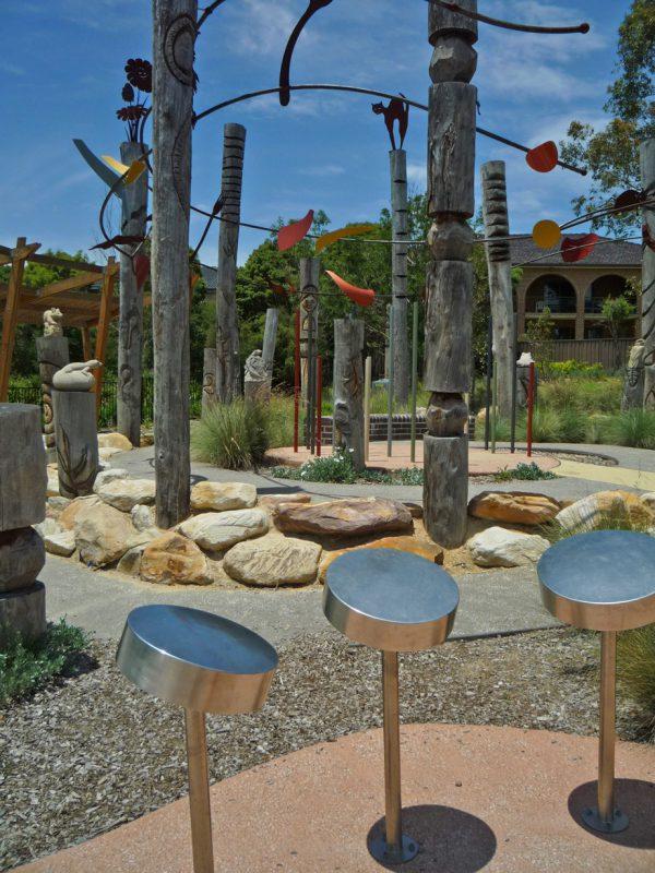 写真:ステンレス製のドラム。奥には動物や模様が刻まれたトーテムポールや石の彫刻が並ぶ小道