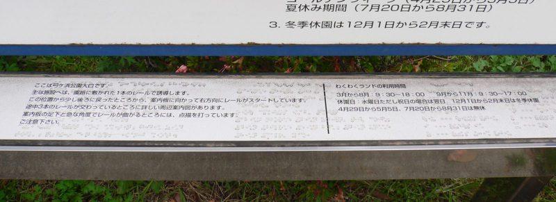 写真:点字の案内。「主な施設へは園路に敷かれた一本のレールで誘導します」などと書かれている