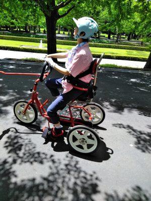 写真:座高が高く背もたれもあるリフトン三輪車に乗る娘さん