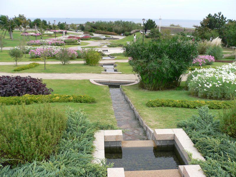 写真:小高い場所から見渡す庭園。中央を水路が流れ、周囲には手入れの生き届いた植物。向こうに海が見える