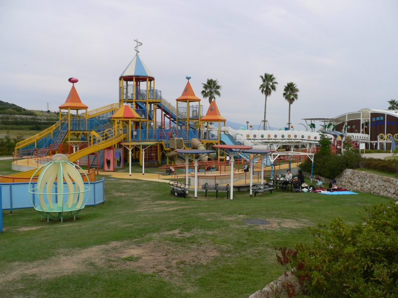 写真:夢っこランドの遠景。大きな複合遊具や遊び場。ベンチのまわりでは家族づれがくつろぐ