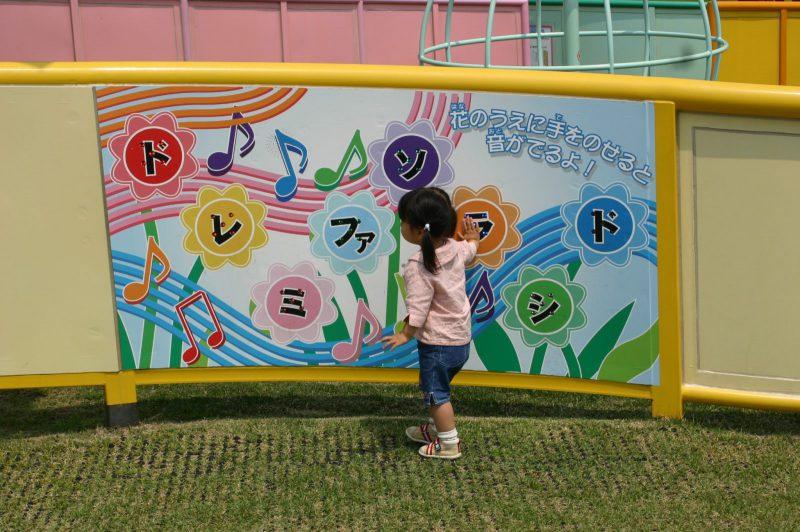 写真:壁に取り付けられた幅180センチほどのパネルとその前に立つ女の子。パネルに描かれた8つの花にはそれぞれドレミファソラシドの文字と、その上に「花のうえに手をのせると音が出るよ!」の説明