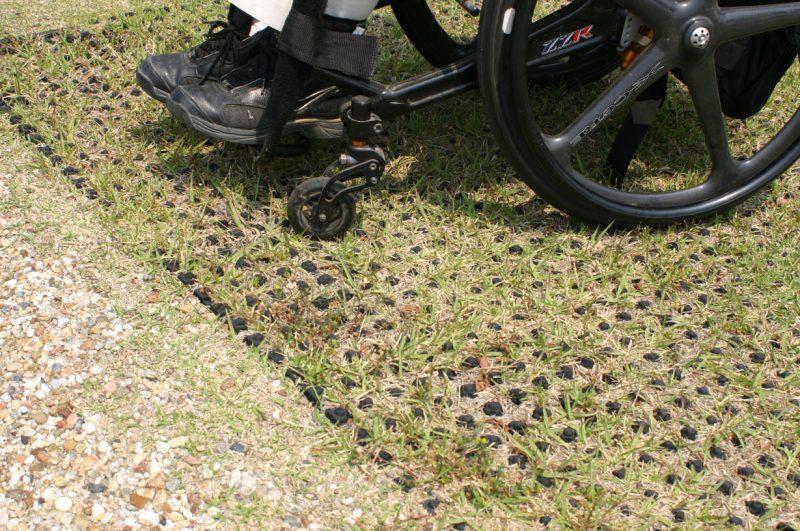 写真:地面に敷かれた芝の保護マットの上を行く車いす